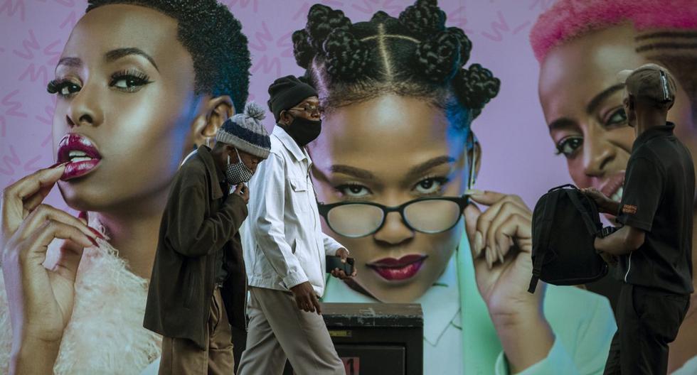En esta fotografía de archivo del lunes 29 de junio de 2020, hombres con mascarillas por el coronavirus pasan junto a una valla publicitaria de productos para el cabello en la calle de Soweto, Sudáfrica. (AP/Themba Hadebe).