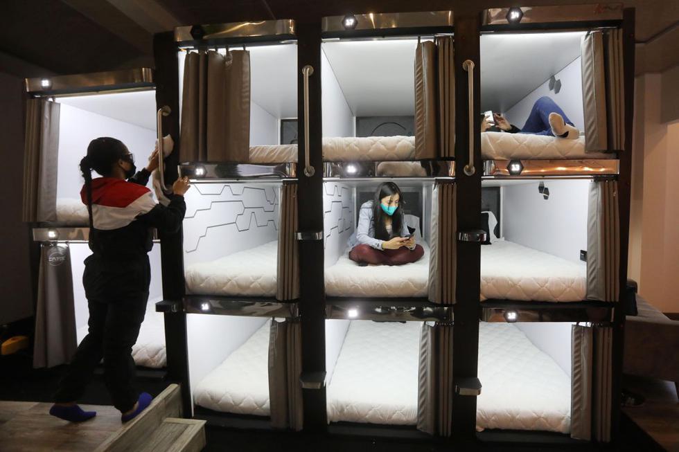 """Una trabajadora desinfecta los dormitorios del hotel tipo cápsula CAPS Future Rooms. Confort y economía es lo que ofrecen emprendedores colombianos que desarrollan un proyecto en el que viajeros y turistas pueden dormir en un hotel que en vez de las tradicionales habitaciones ofrece hospedaje en cápsulas, un """"modelo futurista"""" que ya se emplea en Japón y en China. (EFE/ Carlos Ortega)."""