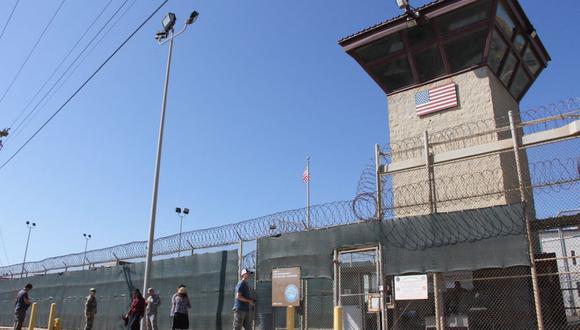La gente pasa por delante de una torre de vigilancia fuera de la cerca del Campo 5 en la Prisión del Ejército de los Estados Unidos en la Bahía de Guantánamo, Cuba, el 26 de enero de 2017. (Thomas WATKINS / AFP).