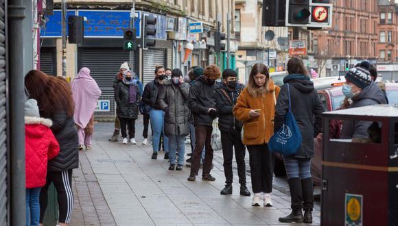 La gente hace cola en la oficina de correos de Crosshill, durante el primer día en el nuevo bloqueo en Glasgow, Escocia, Gran Bretaña. (EFE/Robert Perry).