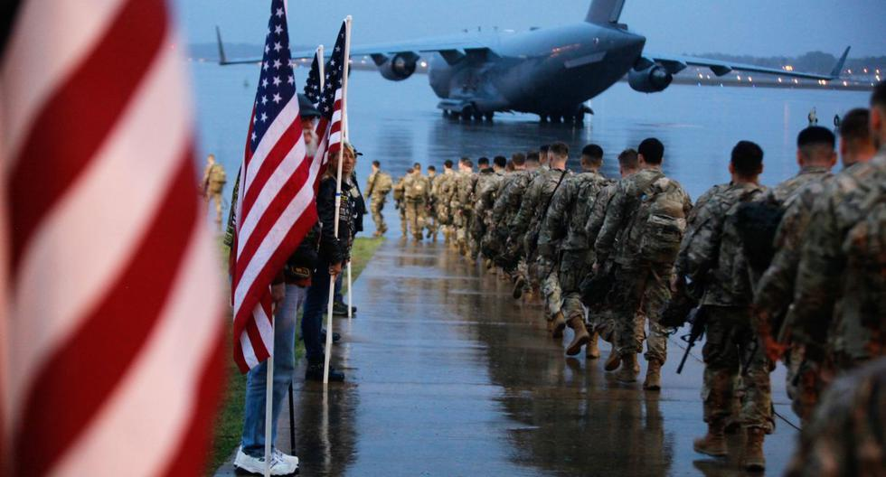 """In this image released by the US Defense Department, 82nd Airborne paratroopers march to board a civilian aircraft bound for the US Central Command area of operations from Fort Bragg, North Carolina, on January 4, 2020. - This deployment is a precautionary action taken to respond to increased threat levels against US personnel and facilities. Thousands more US troops were ordered to the Middle East on January 3 after the US assassinated Iran's military mastermind and Tehran promised """"severe revenge."""" (Photo by Hubert Delaney III / US Department of Defense / AFP) / RESTRICTED TO EDITORIAL USE - MANDATORY CREDIT """"AFP PHOTO / US Army Photo / US Army / Spc. Hubert Delaney III"""" - NO MARKETING - NO ADVERTISING CAMPAIGNS - DISTRIBUTED AS A SERVICE TO CLIENTS"""