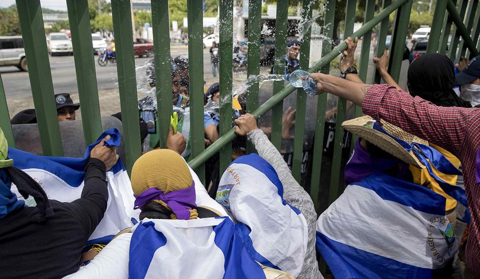 Estudiantes lanzan agua contra agentes antidisturbios durante una protesta en la Universidad Centroamericana (UCA), en Managua (Nicaragua). (Foto: EFE)