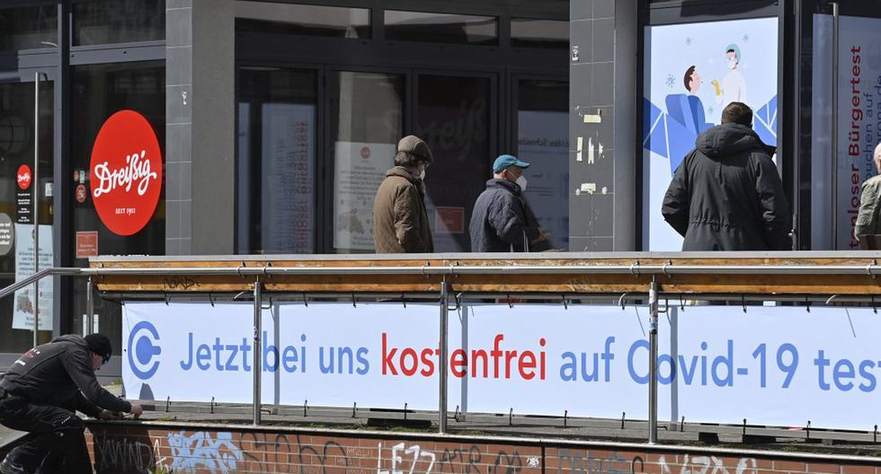 Un trabajador ajusta un letrero cuando la gente se dirige frente a un centro de pruebas de COVID-19 en Berlín (Alemania), el 22 de abril de 2021. (John MACDOUGALL / AFP).