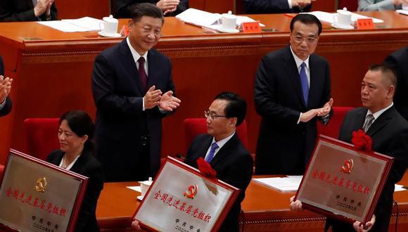 El presidente chino Xi Jinping (izquierda) y el premier chino Li Keqiang (derecha) aplauden al personal que lucha contra el COVID-19 después de entregarle placas y medallas como parte de un homenaje en el Gran Palacio del Pueblo en Beijing. (Foto: EFE / EPA / Wu Hong)