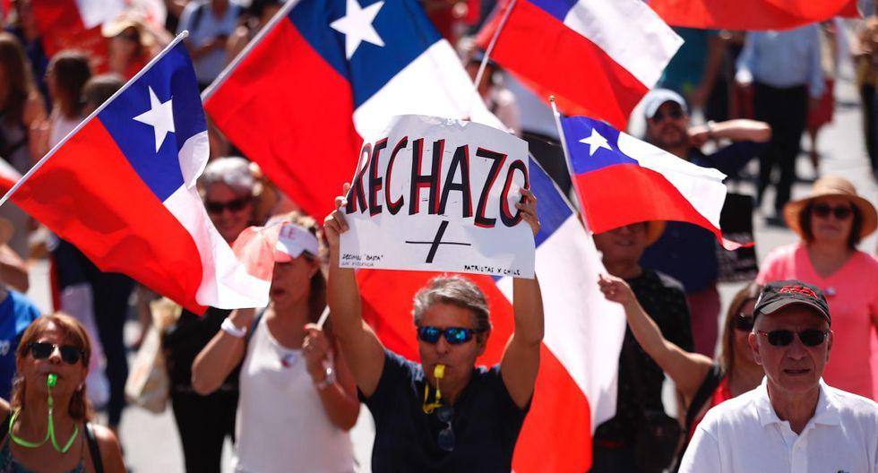 """La mayoría de los manifestantes, vecinos de este barrio, protestó de forma pacífica sin interrumpir el tránsito vehicular, portando pancartas con la frase """"rechazo"""" y banderas chilenas mientras gritaban consignas en contra de la izquierda chilena.  (EFE)."""