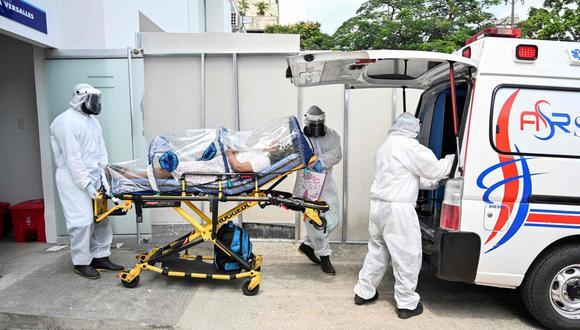 Los trabajadores de la salud trasladan a una paciente de coronavirus novela recuperada de la clínica Versalles a su casa el 24 de junio de 2020. (AFP / Luis ROBAYO).