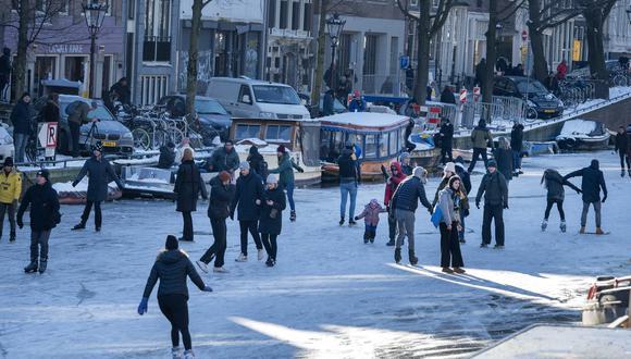 La gente camina y patina sobre hielo en el canal Prinsengracht en Amsterdam. (Foto: Evert Elzinga / EFE)