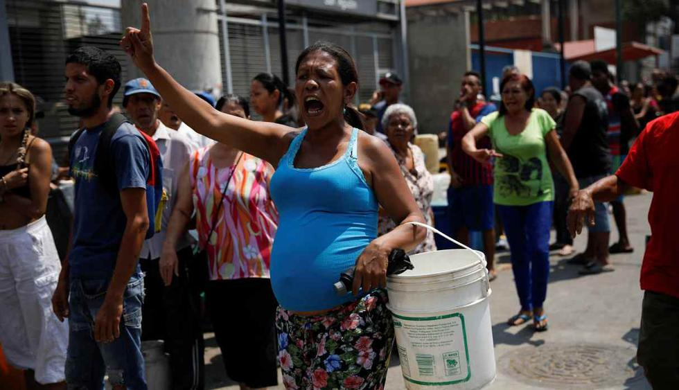 La gente grita mientras hacen cola para tratar de recolectar agua en una calle de Caracas. (Foto: Reuters)