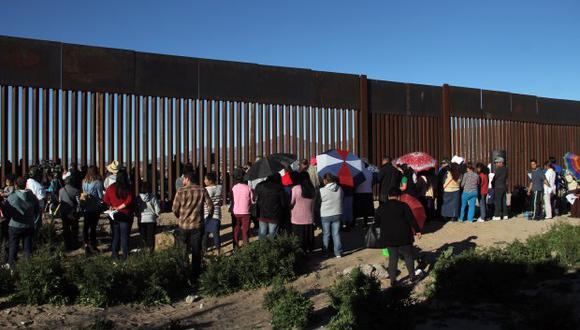 Los residentes de Anapra, un vecindario en las afueras de Ciudad Juárez en México, se reúnen junto a la valla fronteriza. (Foto: AFP)