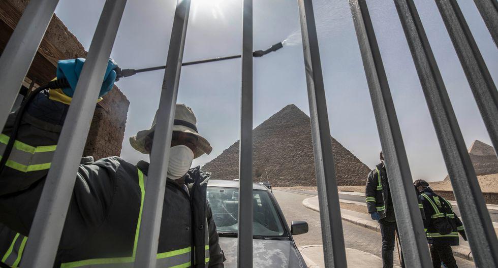 Los trabajadores del municipio egipcio desinfectan la necrópolis de las pirámides de Guiza en las afueras del suroeste de El Cairo. (AFP).