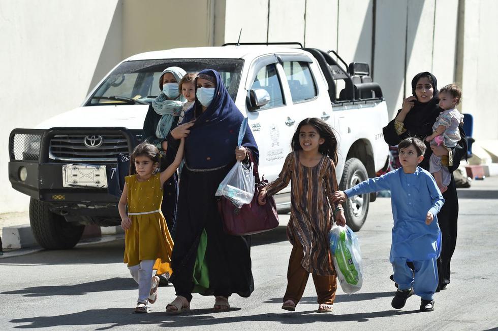 Una mujer afgana con niños, con la esperanza de salir de Afganistán, atraviesa la puerta de entrada principal del aeropuerto de Kabul, Afganistán, el 28 de agosto de 2021. (WAKIL KOHSAR / AFP).