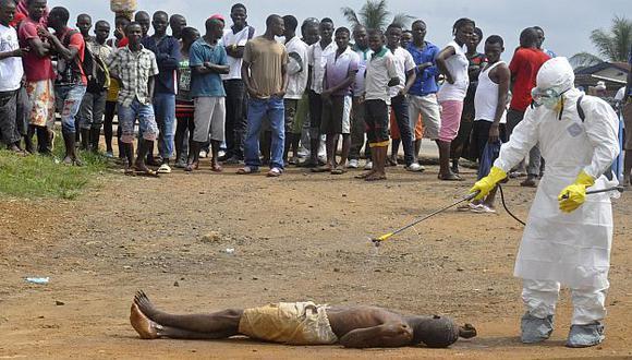 Personal sanitario atiende a un potencial paciente con ébola, abandonado en un calle de Monrovia, capital de Liberia. (AP)