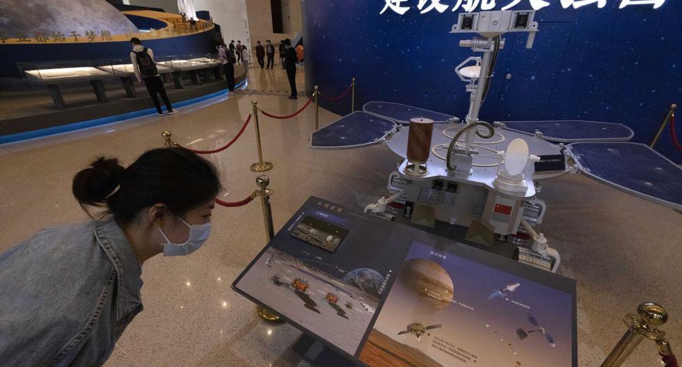 Un visitante de una exposición sobre el programa espacial de China observa un modelo de tamaño real del rover de Marte Zhurong, que lleva el nombre del dios chino del fuego, en el Museo Nacional de Beijing el jueves 6 de mayo de 2021. (AP/Ng Han Guan).