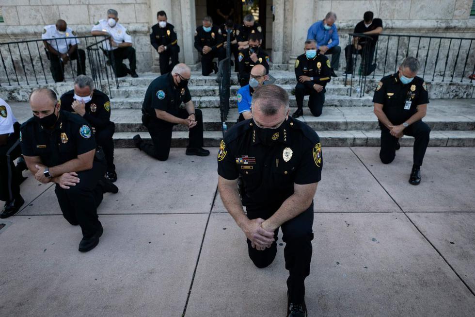 Oficiales de policía se arrodillan durante una manifestación en Coral Gables, Florida, en respuesta a la reciente muerte de George Floyd, un hombre negro desarmado que murió mientras era arrestado y sujetado al suelo por un oficial de policía de Minneapolis. (AFP / Eva Marie UZCATEGUI)