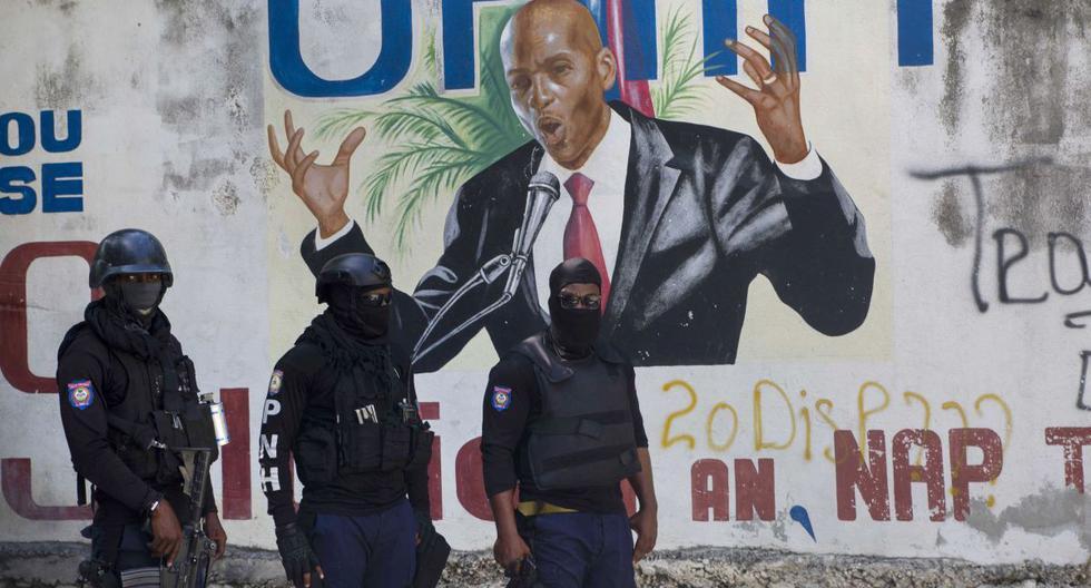 La policía se para cerca de un mural que muestra al presidente haitiano Jovenel Moise, en Puerto Príncipe, Haití, el miércoles 7 de julio de 2021. (AP/Joseph Odelyn).