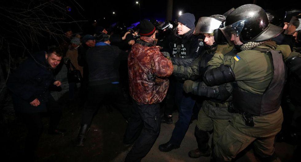 Los policías ucranianos despejan el camino mientras cientos de ciudadanos protestan ante la llegada de un grupo de personas de Wuhan. (Reuters).