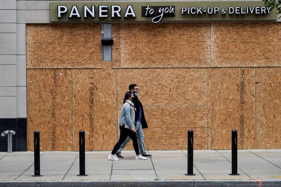 Personas pasan frente a una tienda protegida con tableros de madera en Washington (Estados Unidos). (REUTERS/Joshua Roberts).
