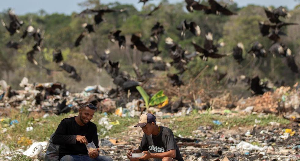 Venezolanos son vistos en el basurero municipal comiendo y en el fondo una bandada de buitres los acechan hoy viernes en la ciudad de Pacaraima, Brasil. (EFE)