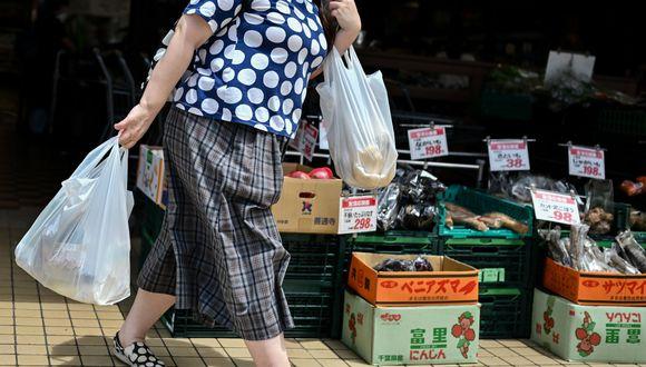 Consumidora carga bolsas de plástico a la salida de un supermercado en Japón. (Foto: AFP)