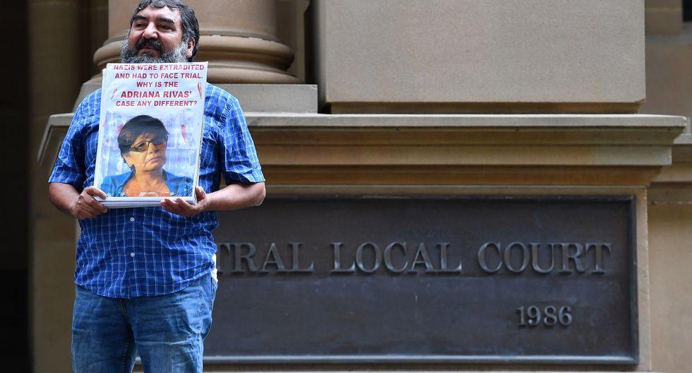 Un miembro de la comunidad australiana chilena sostiene una imagen de una víctima luego de una comparecencia de Adriana Rivas este martes, en Sídney. (Foto: EFE)