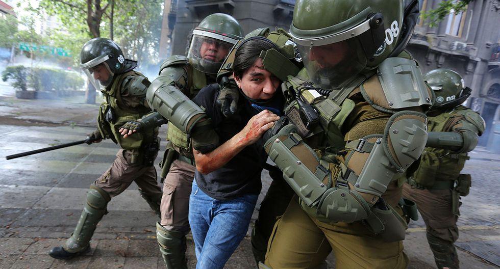 La fuerzas del orden detienen a un manifestante en la Plaza Italia. (Foto: EFE)