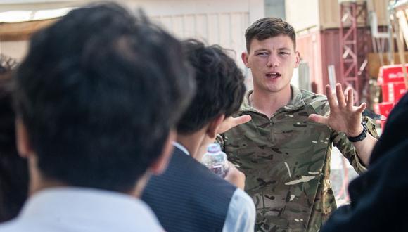 Imagen muestra a un miembro de las Fuerzas Armadas del Reino Unido hablando con personas durante un despliegue para apoyar la evacuación de ciudadanos británicos y personal autorizado en el aeropuerto de Kabul en Afganistán. (Ben SHREAD / MOD / AFP).