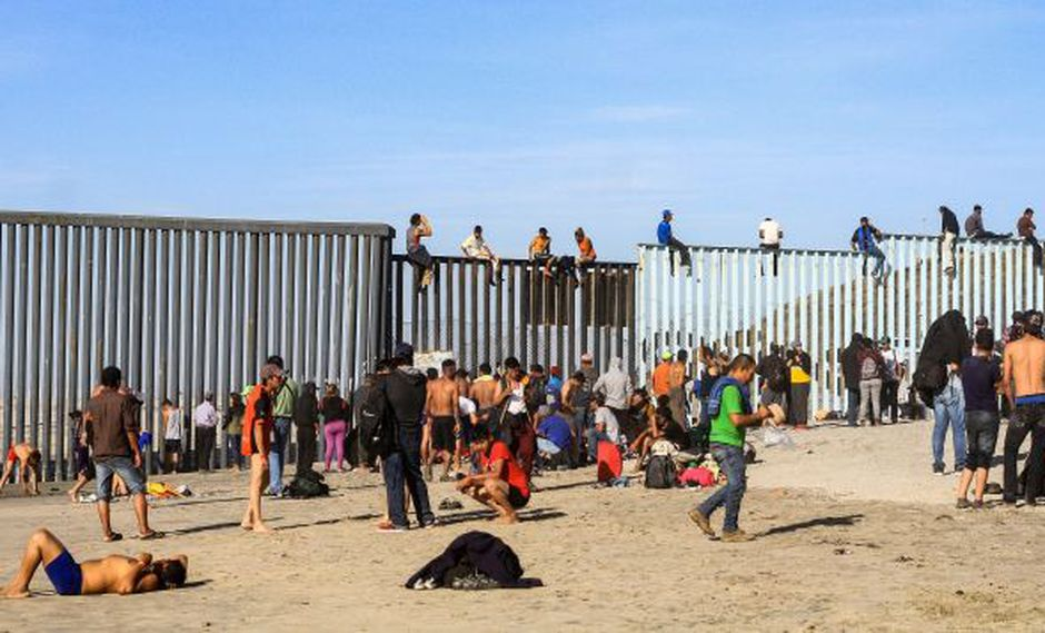 Integrantes de la caravana de centroamericanos escalan el muro fronterizo en Tijuana, en el estado de Baja California (México), el pasado martes. (Foto: EFE)