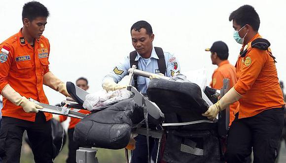 AirAsia: Rescatistas trasladan restos de un asiento del avión siniestrado. (EFE)
