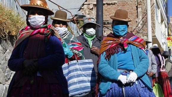 Personas con mascarillas hacen cola para recibir el bono de ayuda del gobierno en Puno (Foto: Carlos Mamani / AFP)