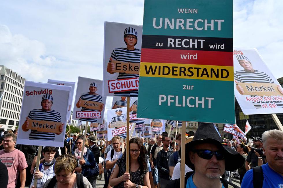 Carteles con la canciller alemana Angela Merkel y ministros como prisioneros se ven durante una manifestación convocada por negadores de extrema derecha y COVID-19 para protestar contra las restricciones relacionadas con la nueva pandemia de coronavirus. (AFP/John MACDOUGALL).